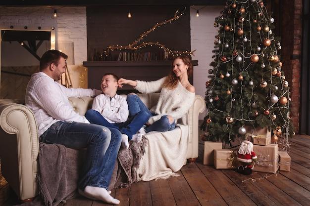 Madre, padre e figlio si divertono sul divano vicino all'albero