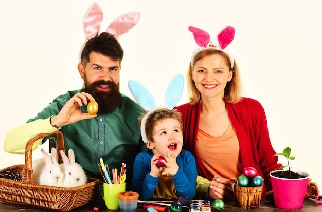 Madre, padre e figlio che dipingono le uova. famiglia felice che si prepara per la pasqua.