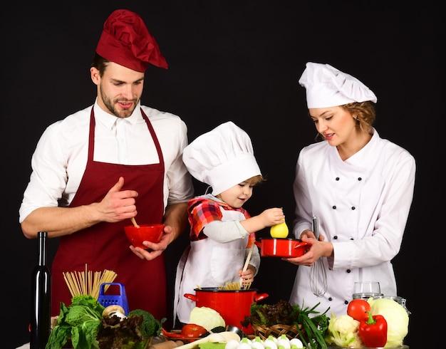Madre e padre che insegnano al ragazzo a cucinare. famiglia felice in cucina. il bambino con i genitori prepara il cibo.