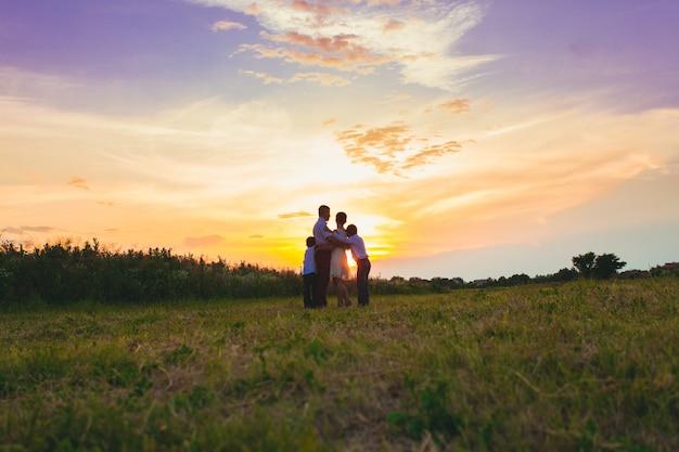 Madre, padre e due figli camminano nel campo e trascorrono il sole, vista da dietro