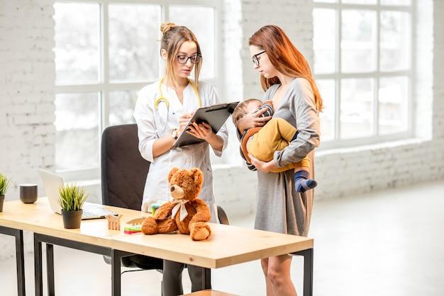 Madre che allatta il suo bambino durante la consultazione con il pediatra della giovane donna in piedi nell'ufficio bianco