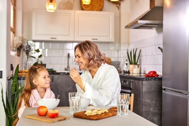 Madre che allatta la figlia con un cucchiaio, mangiando porridge