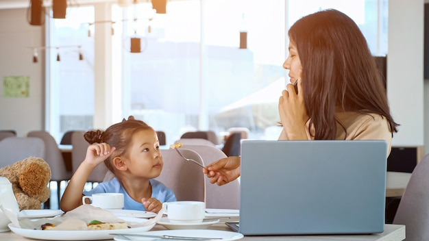 La madre nutre la figlia al ristorante. la mamma asiatica della donna d'affari dà una fetta di pizza al bambino seduto al tavolo con tè e lapto grigio e parla su uno smartphone nero primo piano