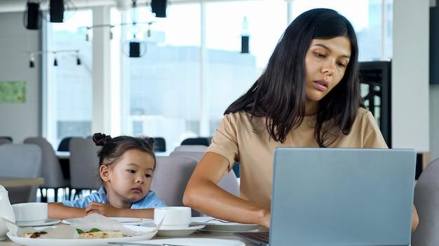 La madre nutre la figlia al ristorante. la mamma asiatica della donna d'affari dà una fetta di pizza al bambino seduto al tavolo con il tè e la vista ravvicinata del computer portatile grigio