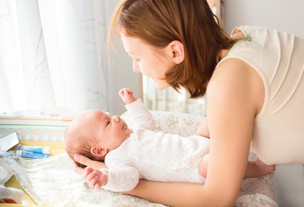 La mamma si prende cura delicatamente del bambino sul fasciatoio a casa