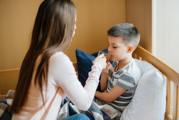 La madre dà il tè caldo al limone al suo bambino durante la malattia e il virus. covid19, coronavirus, pandemia.