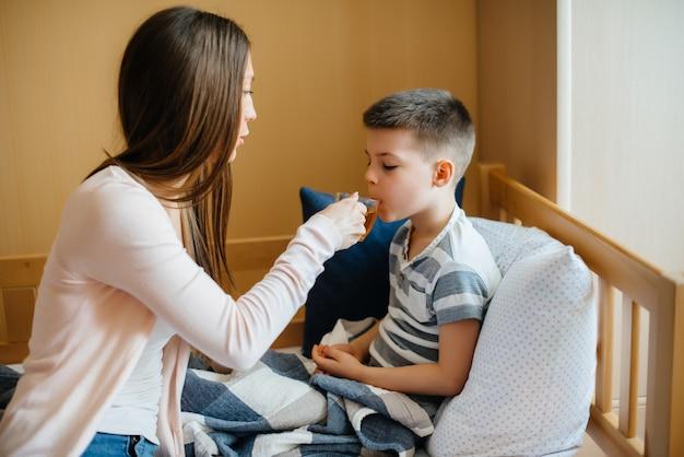 La madre dà il tè caldo al limone al suo bambino durante la malattia e il virus. medicina e cura