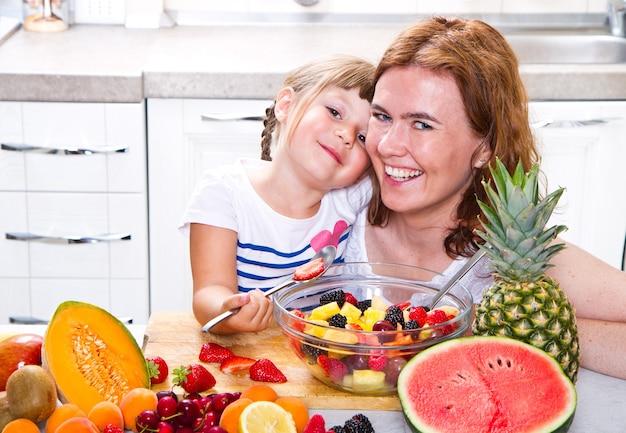 La mamma dà alla bambina una macedonia di frutta in cucina.