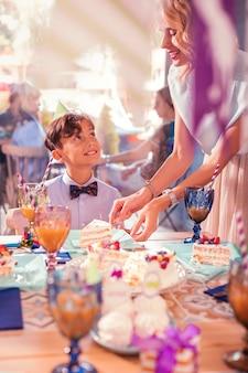 Madre che dà la torta. ragazzo di buon compleanno che sorride e guarda gentilmente la sua madre premurosa mentre ottiene una fetta di torta da lei