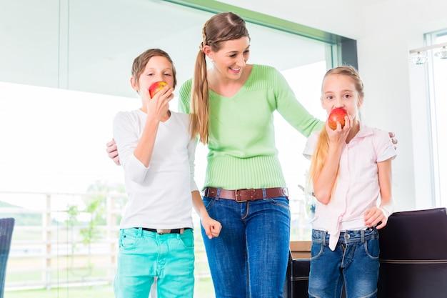 Madre che dà ai bambini mela per una vita sana
