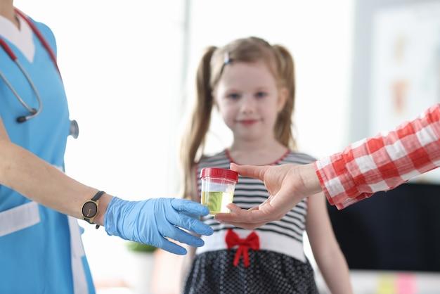 Madre che dà al medico un barattolo di analisi delle urine davanti al primo piano della bambina