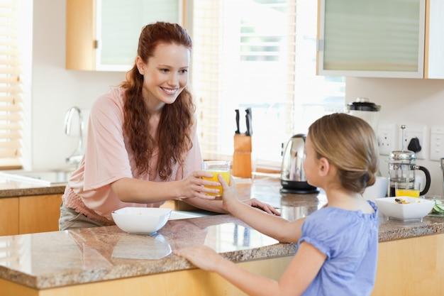 Madre che dà a sua figlia succo d'arancia