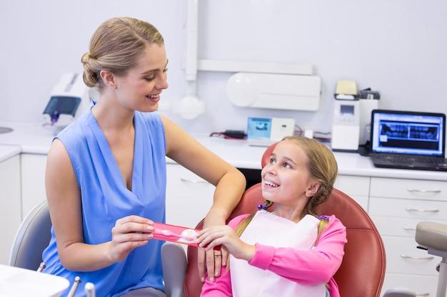 Madre dando spazzolino da denti alla figlia presso la clinica odontoiatrica