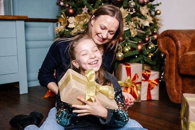 La madre sta per fare una sorpresa per la figlia che fa un regalo, vicino all'albero di natale a casa.