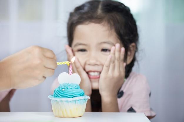 Candela di illuminazione della mano della madre sul bigné di compleanno per la ragazza del bambino che celebra e che soffia le candele sul compleanno