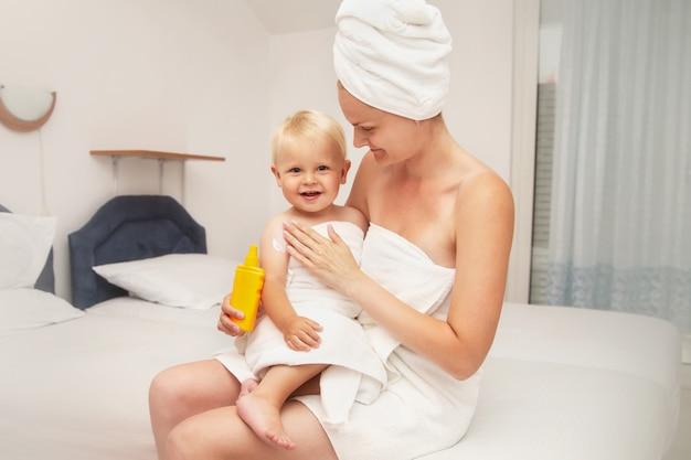 La madre e il bambino infantile felice in asciugamani bianchi dopo il bagno applicano la crema solare o dopo la crema solare