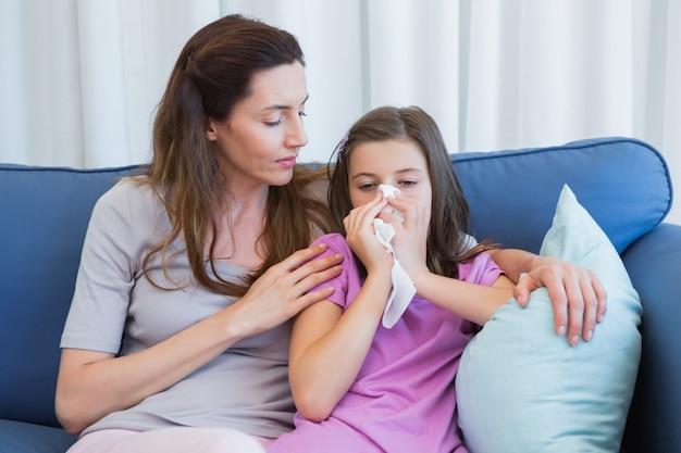 Madre che aiuta la figlia a soffiarsi il naso