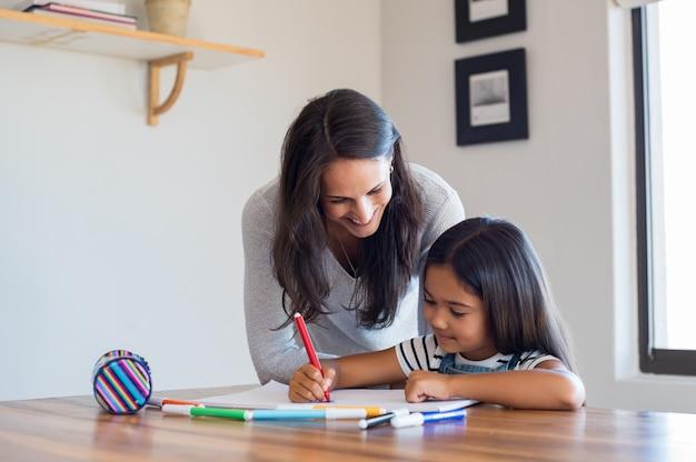 La madre aiuta la figlia a disegnare
