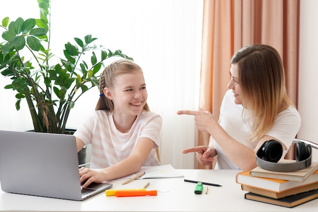 Figlia d'aiuto della madre per fare i compiti. il concetto di educazione domestica in quarantena. divertimento durante l'apprendimento a distanza