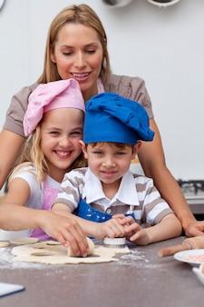 Madre che aiuta i suoi bambini a cuocere