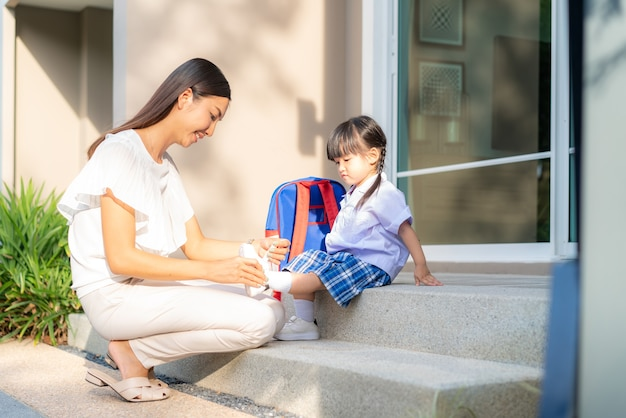 Madre che aiuta sua figlia a mettere le scarpe o decollare al parco all'aperto per prepararsi