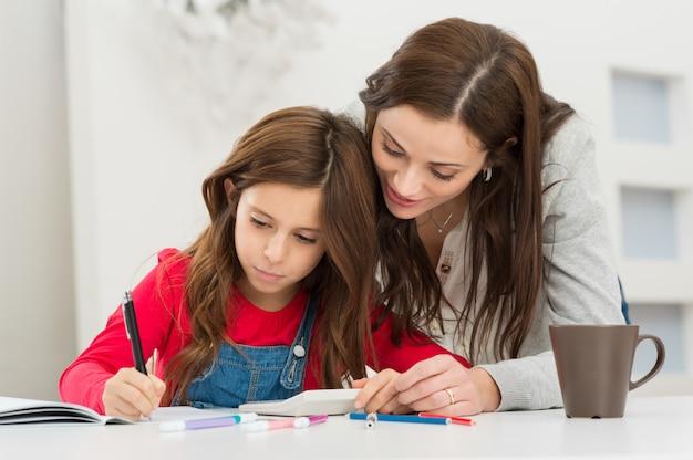 Madre che aiuta sua figlia mentre studia