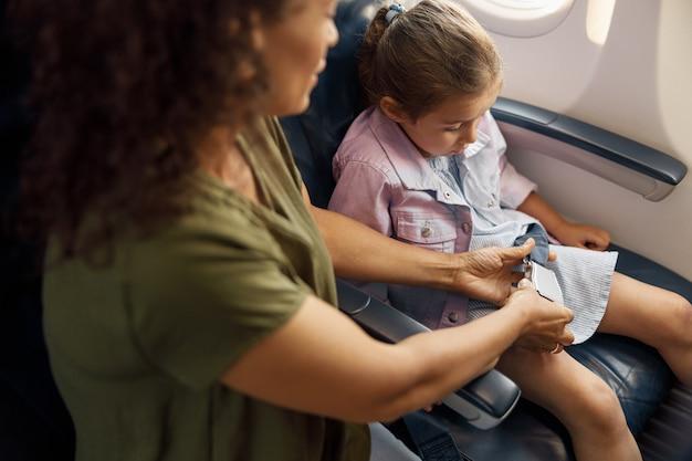 Madre che aiuta la sua piccola figlia a regolare e stringere la cintura di sicurezza su un aereo per un volo sicuro. viaggiare in aereo durante covid19, concetto di famiglia