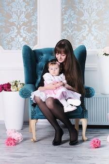 La madre e il suo bambino a casa seduti in poltrona