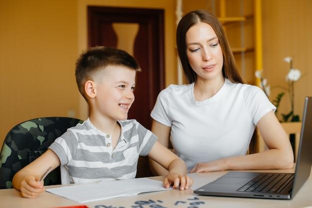 Una madre e suo figlio sono impegnati nell'apprendimento a distanza a casa davanti al computer. resta a casa, allenandoti.