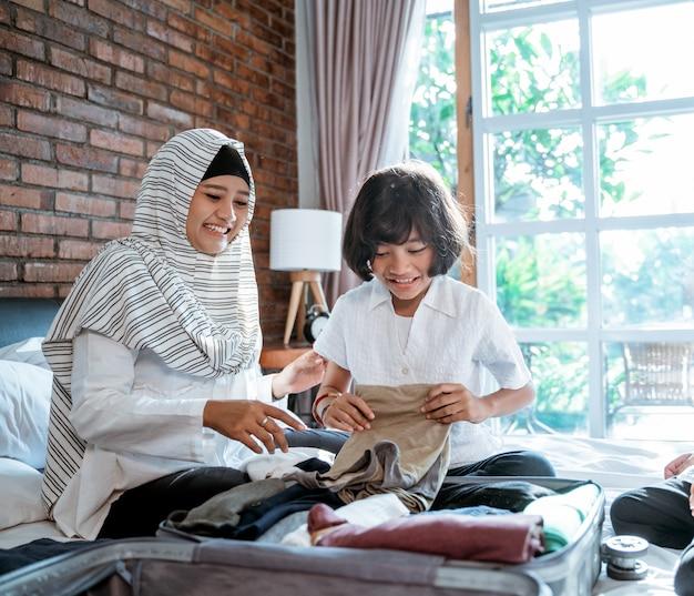 La madre e il bambino preparano i vestiti e li mettono in valigia per essere trasportati quando mudik