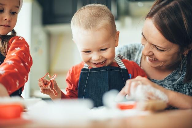 Madre e figli che cuociono i biscotti per natale a casa indossando abiti rossi e babbo natale sorridendo