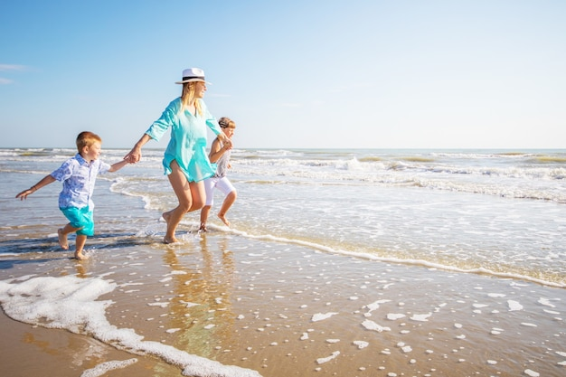 La mamma e i suoi bambini giocano sulla spiaggia