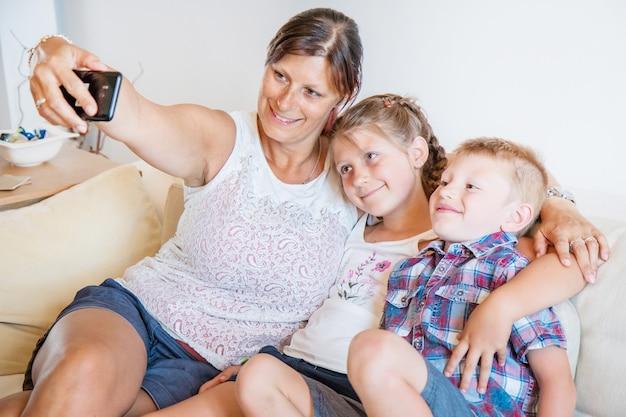 Madre e figli che prendono un selfie sul divano.famiglia felice