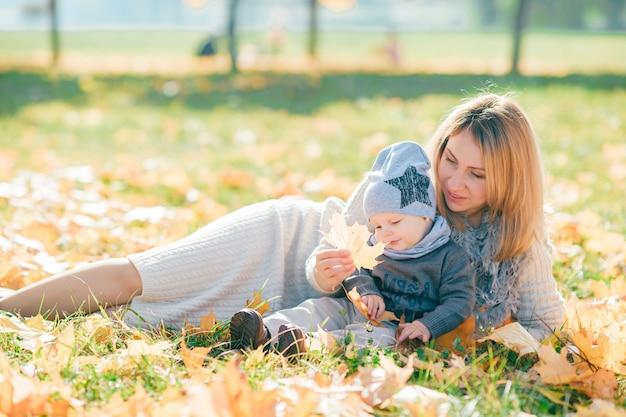 Generi e il suo bambino sveglio nel parco di autunno.