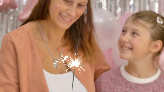 La madre e la figlia stanno guardando la scintilla bruciare alla festa di compleanno