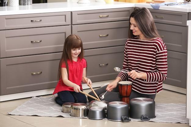 Madre e figlia che suonano la batteria in cucina