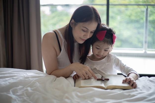 Madre e figlia che leggono dalla bibbia e pregano in ginocchio vicino al letto