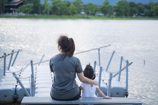 Madre e figlia sedute e guardando il fiume