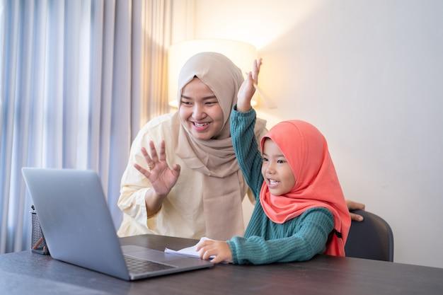 Madre e figlia agitano la mano verso il computer portatile durante la riunione di classe con la scuola da casa