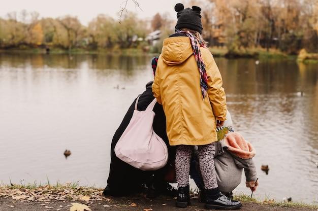 La madre e la sua bambina stanno dando da mangiare alle anatre in uno stagno e ammirando il paesaggio autunnale durante una passeggiata nel parco autunnale. il concetto di un viaggio locale familiare.vista posteriore e dietro