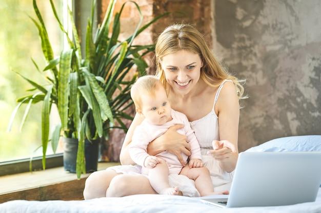 La madre e il suo bambino piccolo a casa. madre con il suo bambino guardando qualcosa sul computer portatile.