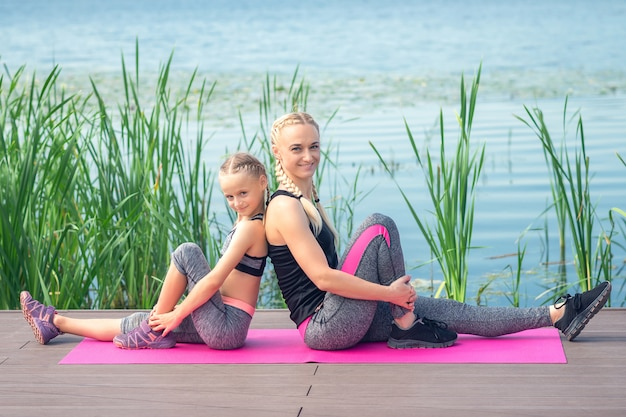 La madre e la figlia piccola sono sedute fianco a fianco sul tappeto rosa vicino al lago su un molo