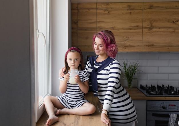 Madre e la sua piccola figlia sono sedute sul davanzale della finestra in cucina e bevono latte