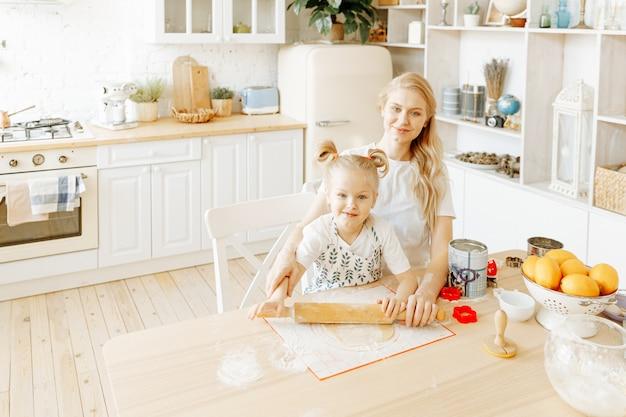 Una madre e sua figlia preparano insieme la pasta da forno nella loro cucina di casa.