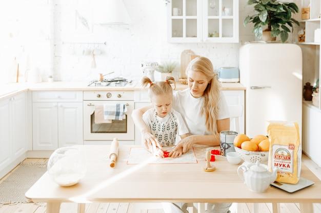 Una madre e sua figlia preparano insieme la pasta da forno nella loro cucina di casa. Foto Premium