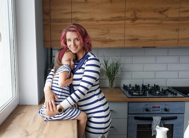 Madre e la sua piccola figlia che si siedono sul davanzale della finestra e si abbracciano dolcemente