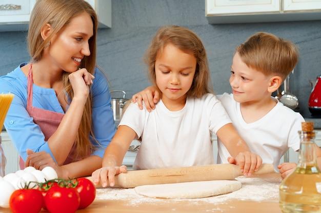 Madre e figli piccoli, ragazzo e ragazza, l'aiutano a preparare la pasta