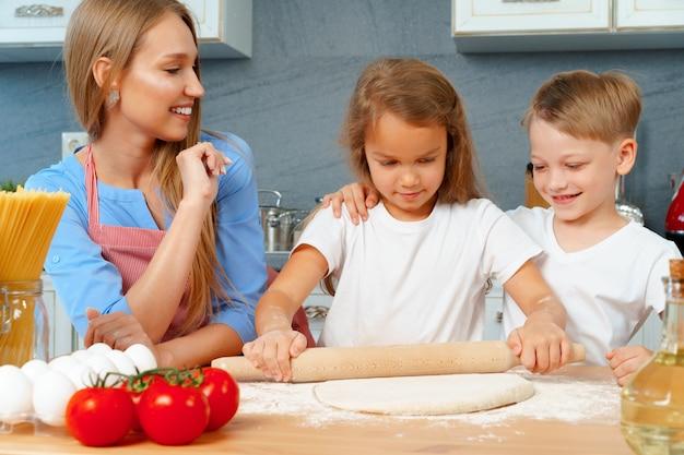 Madre e i suoi bambini piccoli, ragazzo e ragazza, l'aiutano a preparare la pasta
