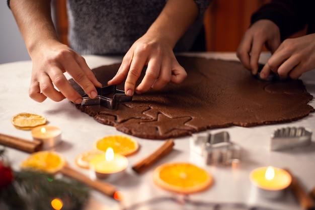 La madre e il suo figlioletto tagliano la pasta in diverse forme per cuocere i biscotti di natale