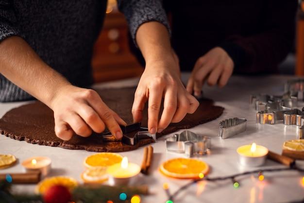 Madre e figlio fanno i biscotti con decorazioni natalizie intorno
